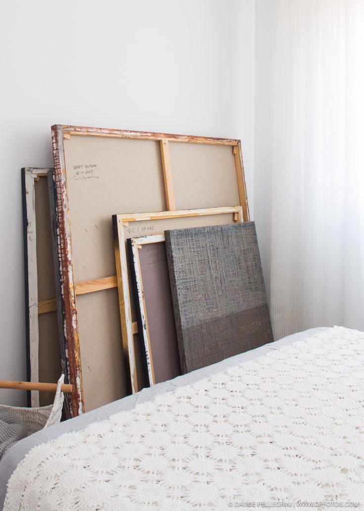 Cuadros apoyados en la pared a los pies de cama